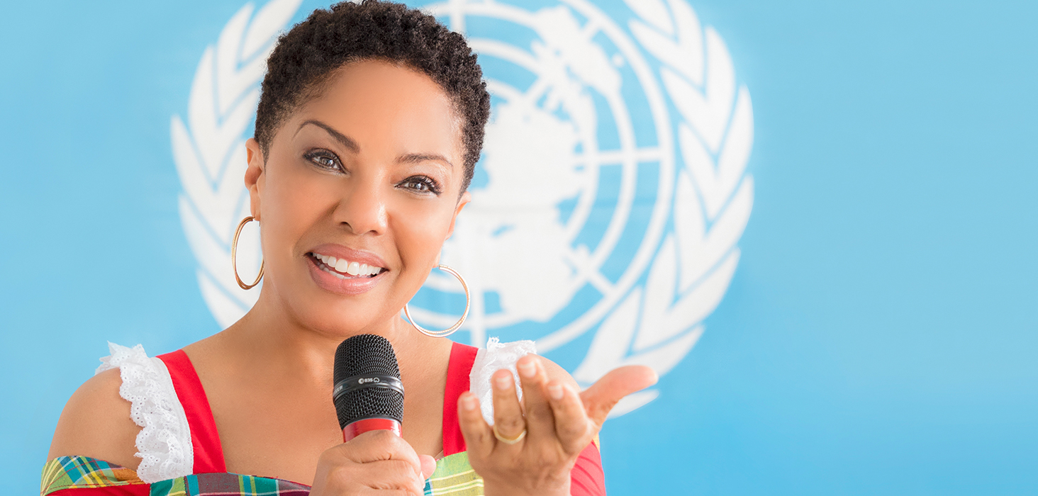 Angela speaking in front of a United Nations flag
